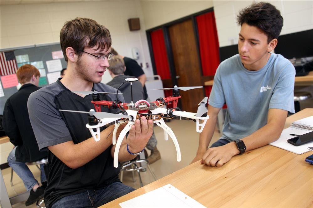 Students work with drones during class.